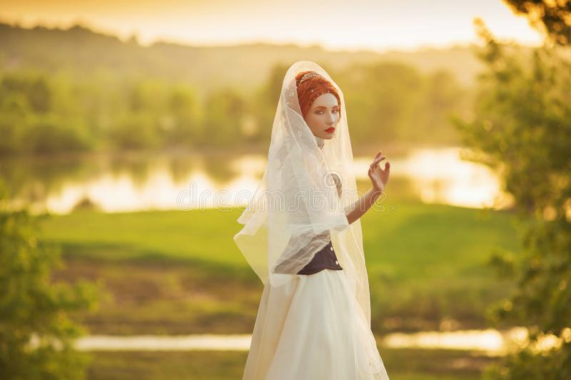 Young renaissance princess on veil on nature background. Virgin woman. Rococo queen in white dress against backdrop of sunset. stock image