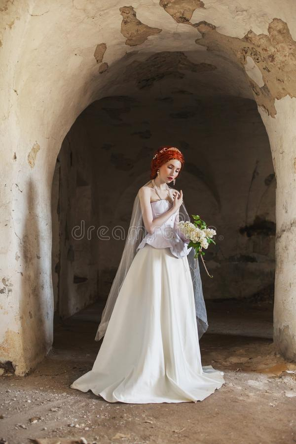 Young renaissance redhead princess with hairstyle in old castle. Doll in the corset. Victorian princess in palace. Fabulous rococo stock photo