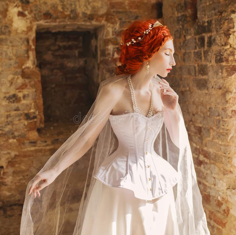Young renaissance redhead princess with hairstyle in the old castle. Fabulous rococo queen in white dress against the backdrop of stock photo
