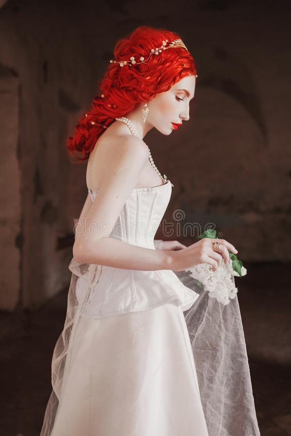 Young renaissance redhead princess with hairstyle in the old castle. Fabulous rococo queen in white dress against the backdrop of royalty free stock photos