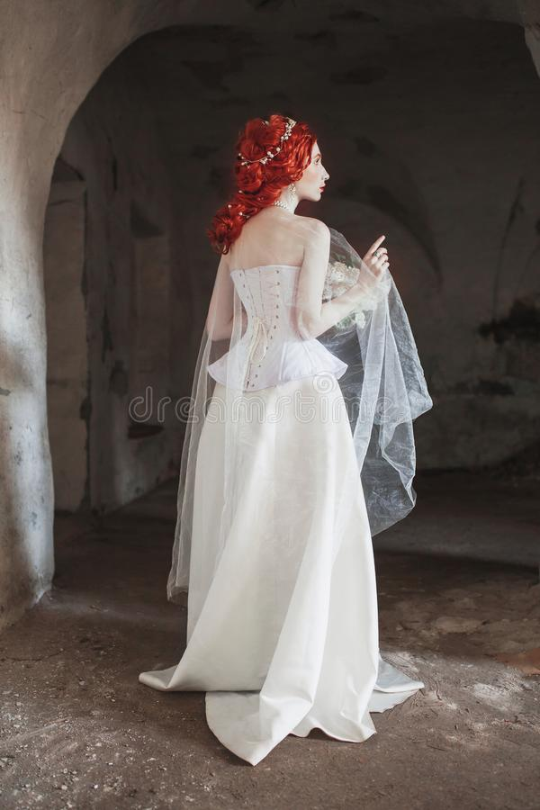 Young renaissance redhead princess with hairstyle in the old castle. Fabulous rococo queen in white dress against the backdrop of. Old stone wall. Doll in the stock photography