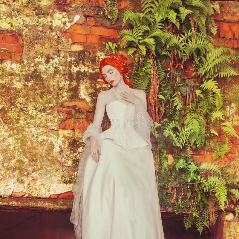 Young renaissance redhead princess with hairstyle in the old castle. Fabulous rococo queen in white dress against the backdrop of stock image