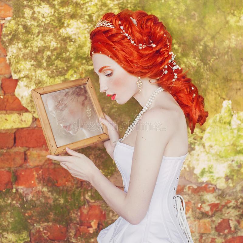 Young renaissance redhead princess with hairstyle in the old castle. Fabulous rococo queen in white dress against the backdrop of stock images