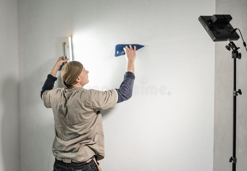 Young repairman aligns with plastic spatula. Worker glueing wallpapers on concrete wall. Repair the apartment. Home royalty free stock photo
