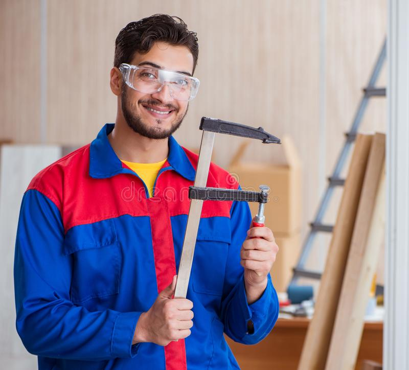 Young repairman carpenter working with clamps stock photos