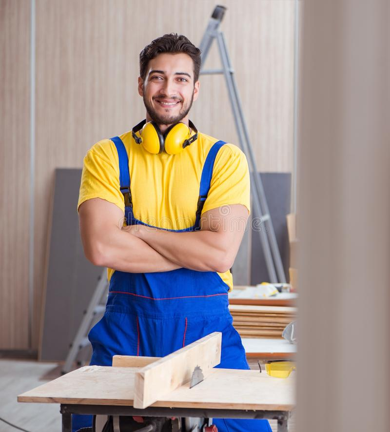 Young repairman carpenter working cutting wood on circular saw royalty free stock images