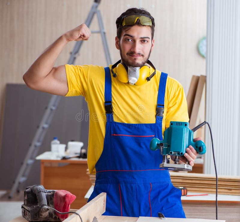 Young repairman carpenter working with power tools electric poli. Sher royalty free stock photo