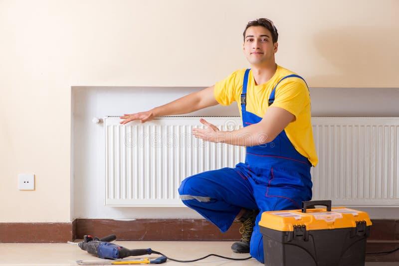The young repairman contractor repairing heating panel. Young repairman contractor repairing heating panel stock photo