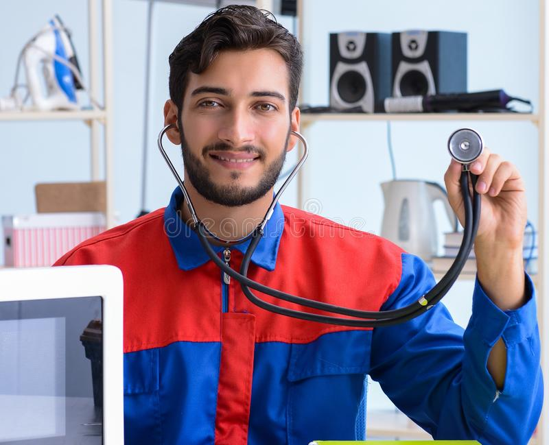 Young repairman fixing and repairing microwave oven stock images