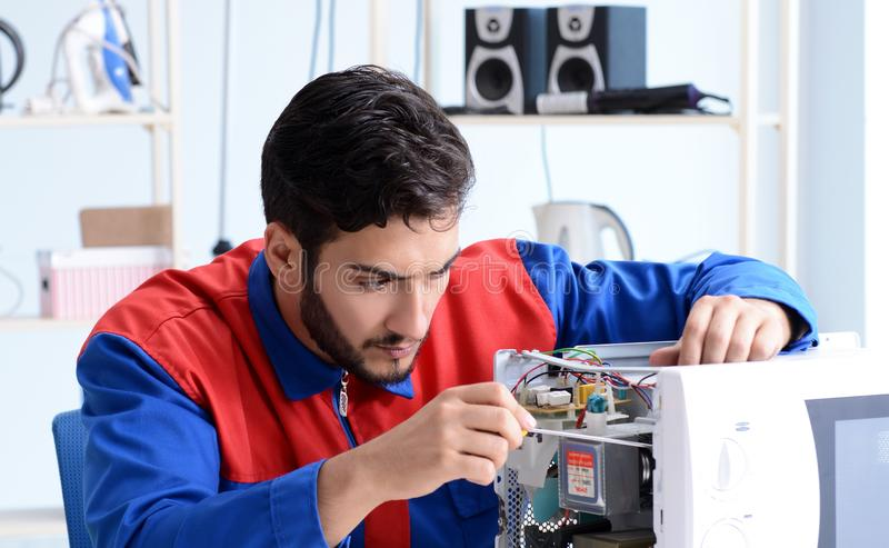 Young repairman fixing and repairing microwave oven stock photo