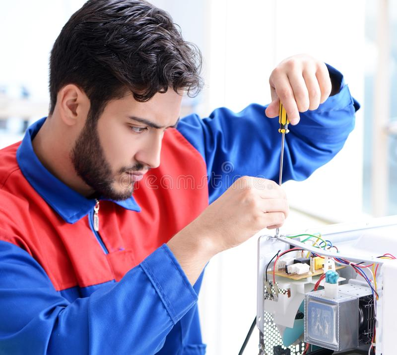 Young repairman fixing and repairing microwave oven royalty free stock photos