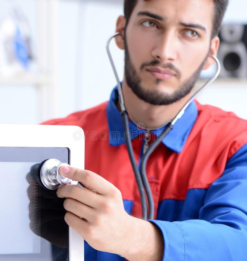 Young repairman fixing and repairing microwave oven stock photos