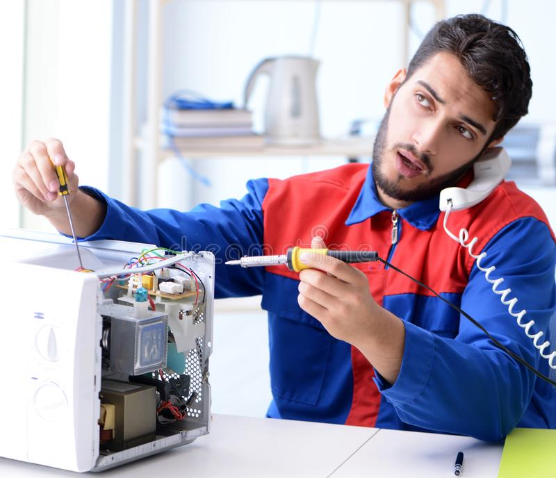Young repairman fixing and repairing microwave oven royalty free stock image