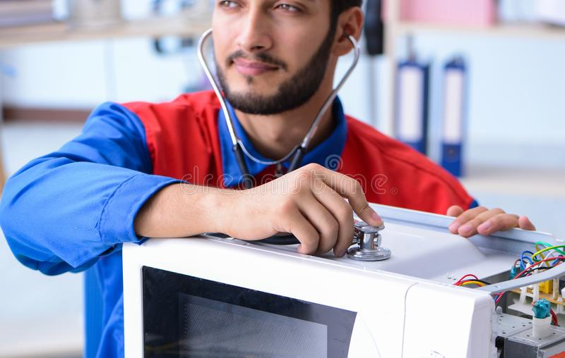 Young repairman fixing and repairing microwave oven. The young repairman fixing and repairing microwave oven stock photo