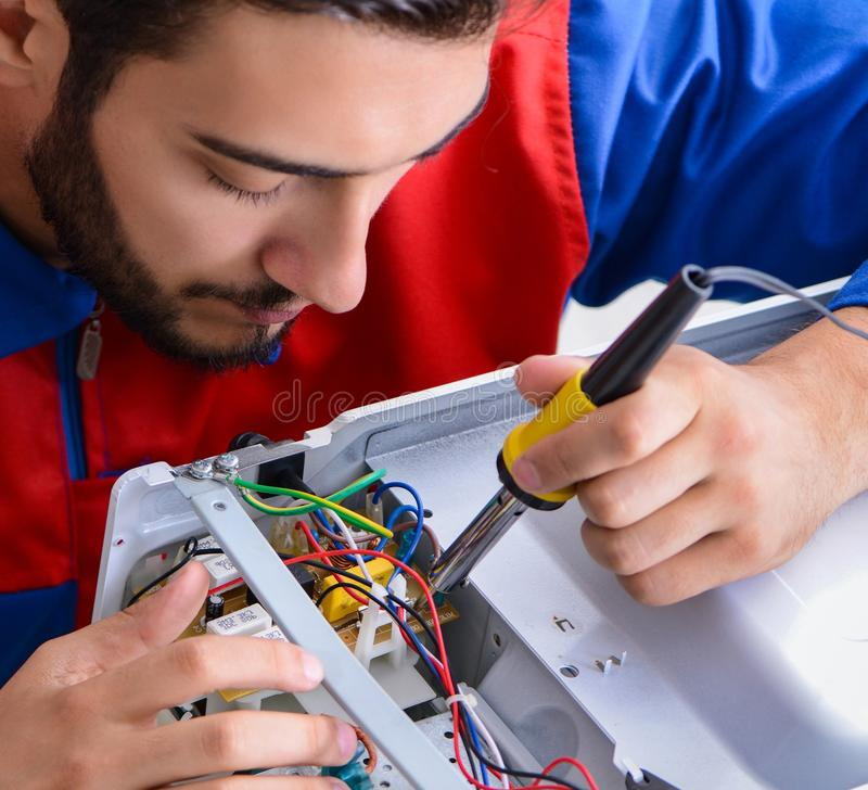 Young repairman fixing and repairing microwave oven. The young repairman fixing and repairing microwave oven stock photos