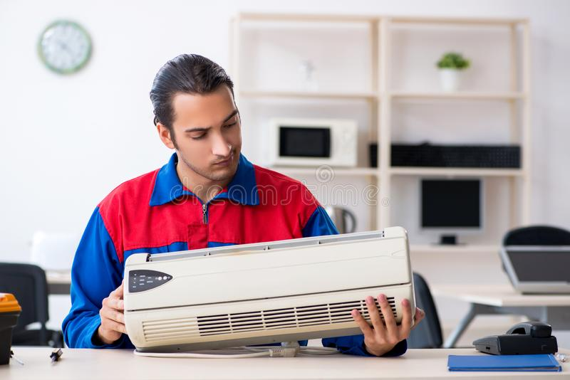 Young repairman repairing air-conditioner at warranty center stock photography