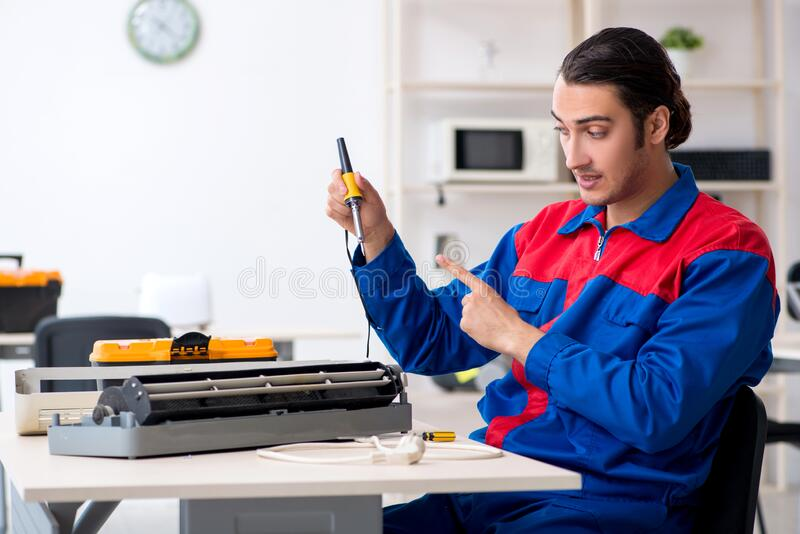 Young repairman repairing air-conditioner at warranty center royalty free stock photos