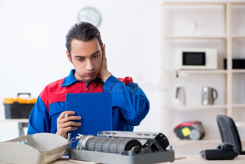 Young repairman repairing air-conditioner at warranty center stock images