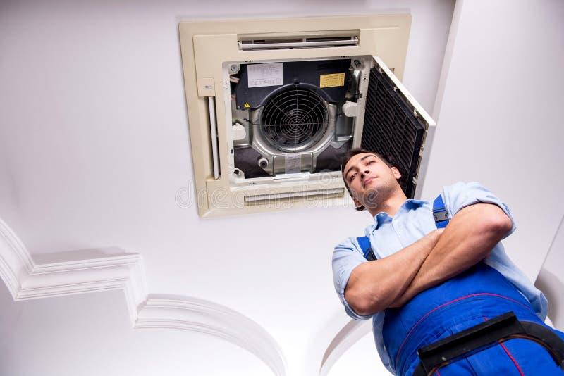 The young repairman repairing ceiling air conditioning unit. Young repairman repairing ceiling air conditioning unit royalty free stock images