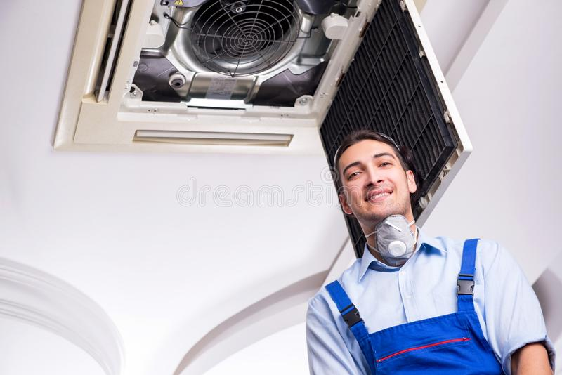Young repairman repairing ceiling air conditioning unit stock photography