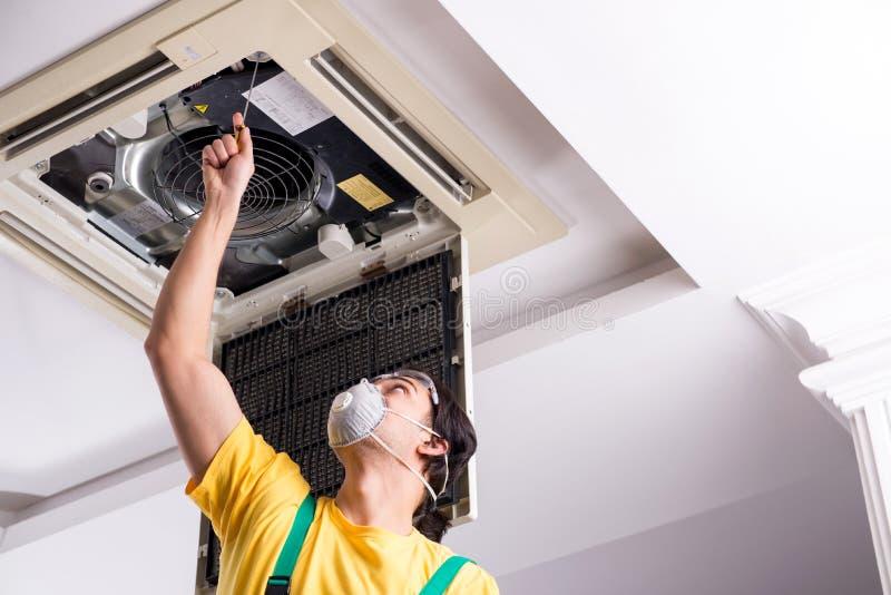 Young repairman repairing ceiling air conditioning unit. The young repairman repairing ceiling air conditioning unit stock photography