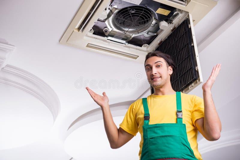 Young repairman repairing ceiling air conditioning unit. The young repairman repairing ceiling air conditioning unit stock photo