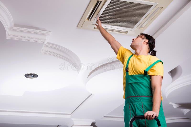 Young repairman repairing ceiling air conditioning unit. The young repairman repairing ceiling air conditioning unit royalty free stock photos