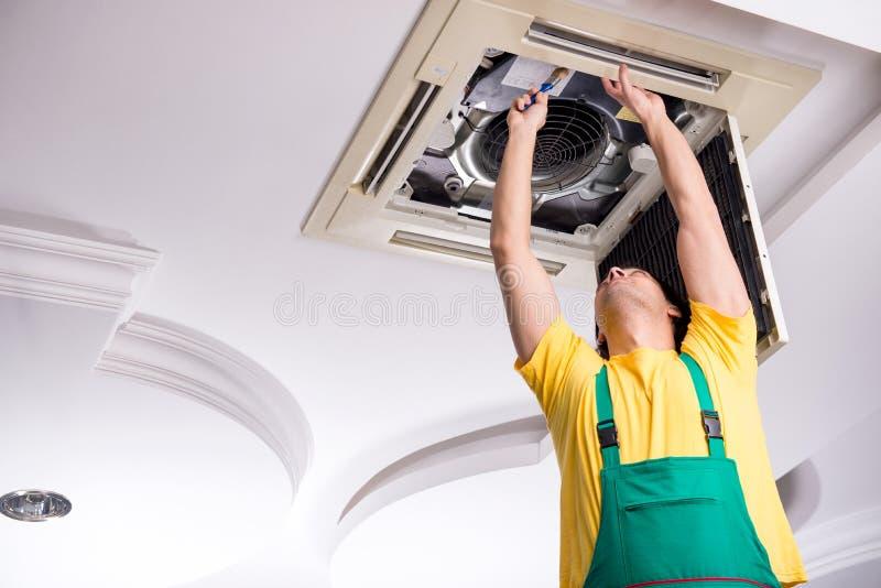 Young repairman repairing ceiling air conditioning unit. The young repairman repairing ceiling air conditioning unit stock photos
