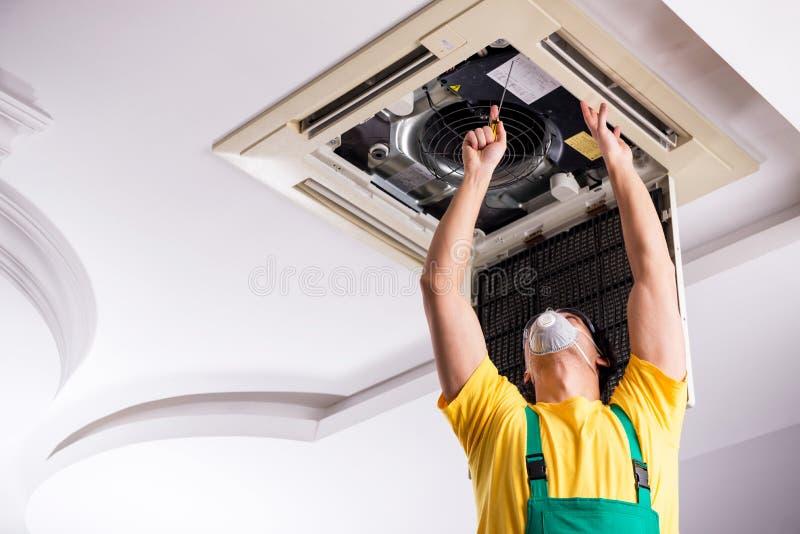 Young repairman repairing ceiling air conditioning unit. The young repairman repairing ceiling air conditioning unit stock images