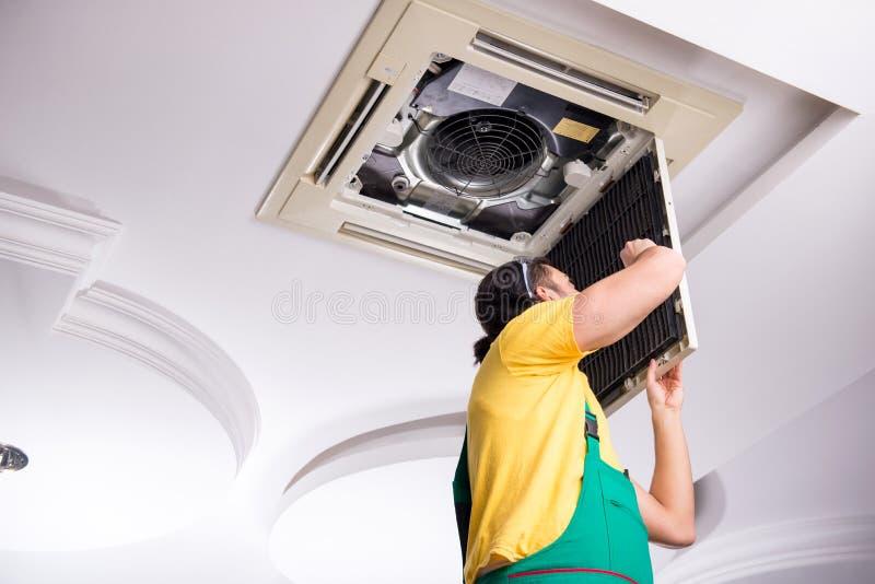 Young repairman repairing ceiling air conditioning unit. The young repairman repairing ceiling air conditioning unit royalty free stock photography