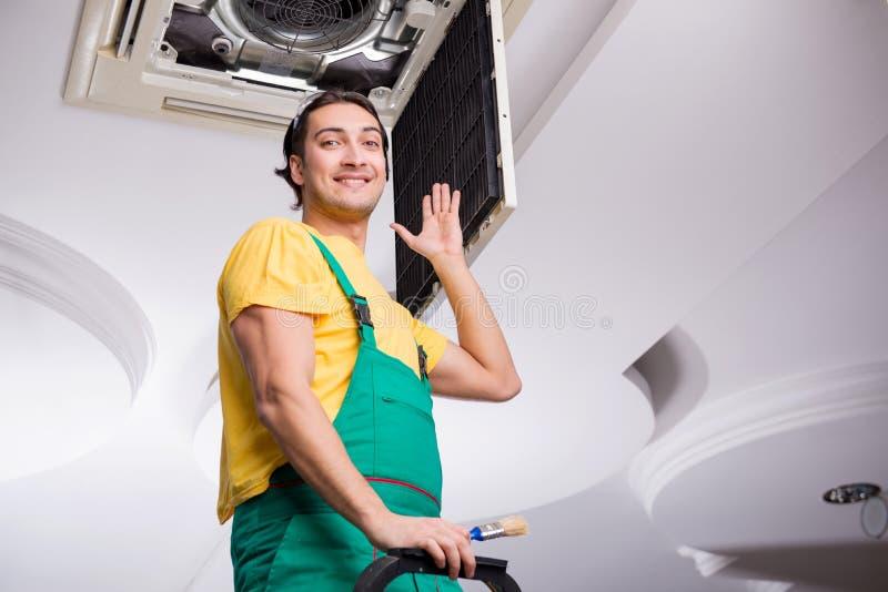 Young repairman repairing ceiling air conditioning unit. The young repairman repairing ceiling air conditioning unit royalty free stock images