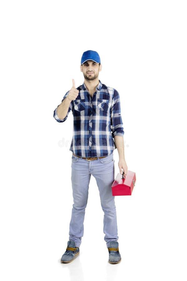 Young repairman show thumb up on studio stock photo