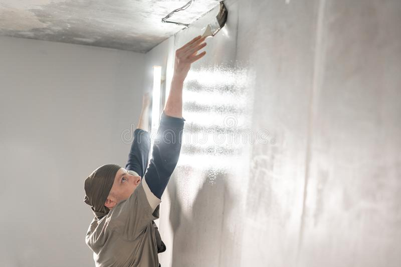 Young repairman smear on wall glue with a brush. Worker glueing wallpapers on concrete wall. Repair the apartment. Home royalty free stock image