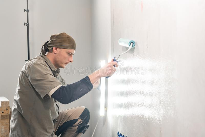 Young repairman smear on wall glue with a roller. . Worker glueing wallpapers on concrete wall. Repair the apartment stock photo