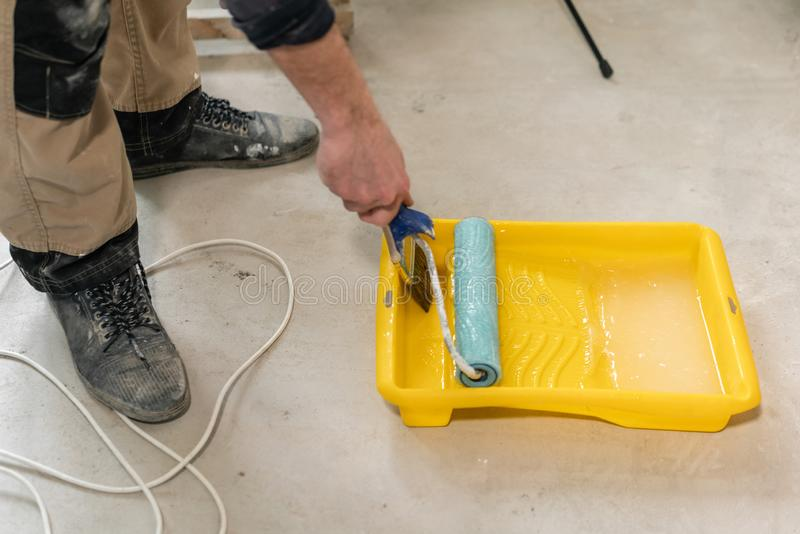 Young repairman smear on wall glue with a roller. . Worker glueing wallpapers on concrete wall. Repair the apartment royalty free stock image
