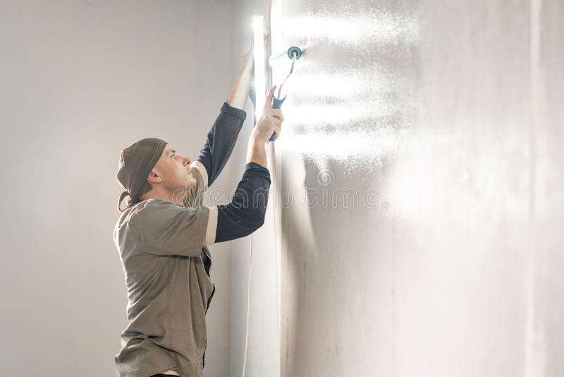 Young repairman smear on wall glue with a roller. . Worker glueing wallpapers on concrete wall. Repair the apartment stock image