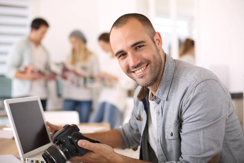 Young reporter working at office on laptop. CHeerful reporter working in office on laptop royalty free stock images