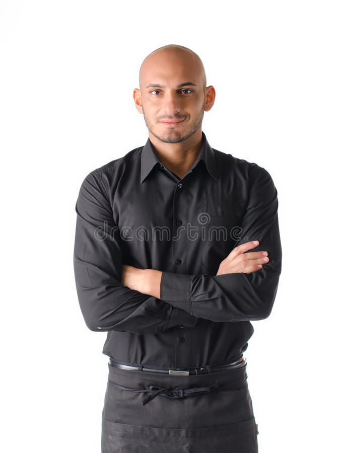 Young restaurant or bar waiter, standing on white, arms crossed stock image