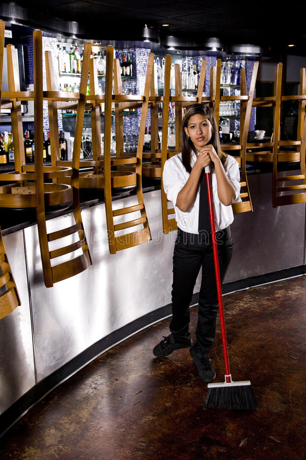 Young restaurant worker cleaning up. Hispanic female worker sweeping floor of closed restaurant stock images