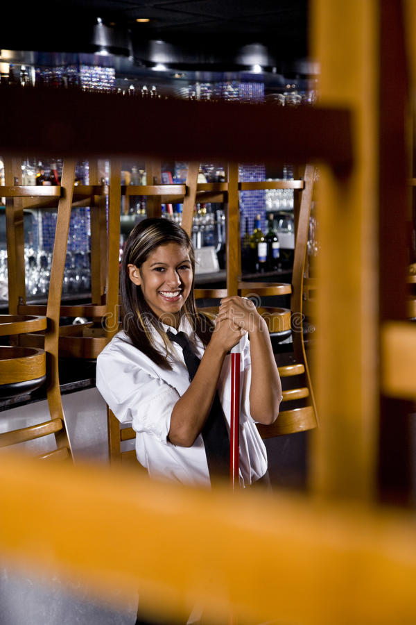 Young restaurant worker cleaning up. Pretty young Hispanic female worker with a broom in a closed bar royalty free stock photography