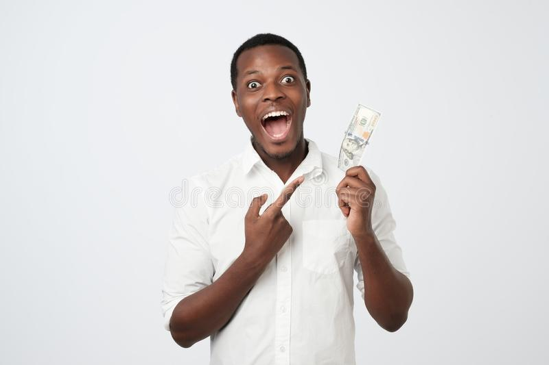 Young rich african american man in shirt holding one hundred dollar with surprise royalty free stock images
