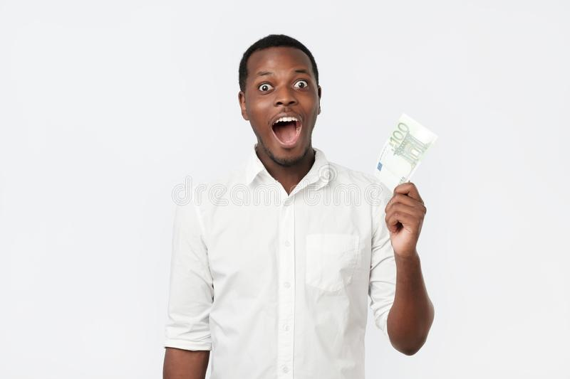 Young rich african american man in shirt holding one hundred euro with surprise. Isolated over white wall royalty free stock images