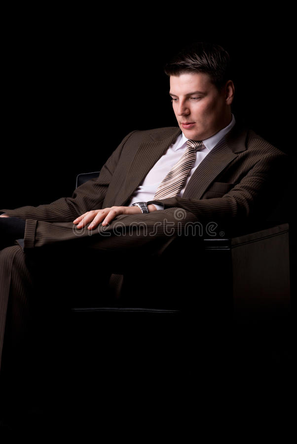 Young rich businessman sitting in armchair stock photography