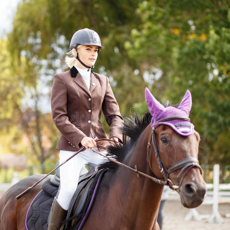 Young rider girl on horse at dressage competition. Equestrian sport background royalty free stock image