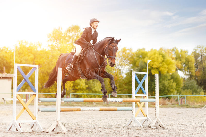 Young rider girl on horse show jumping competition. Young rider girl performing jump at horse show jumping competition. Equestrian sport background stock photo