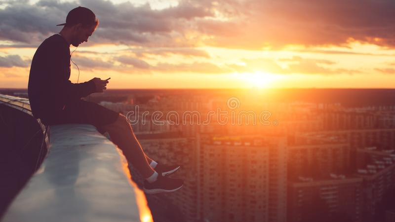Young risky man chilling above the city with smartphone at sunset. Outdoors royalty free stock photos