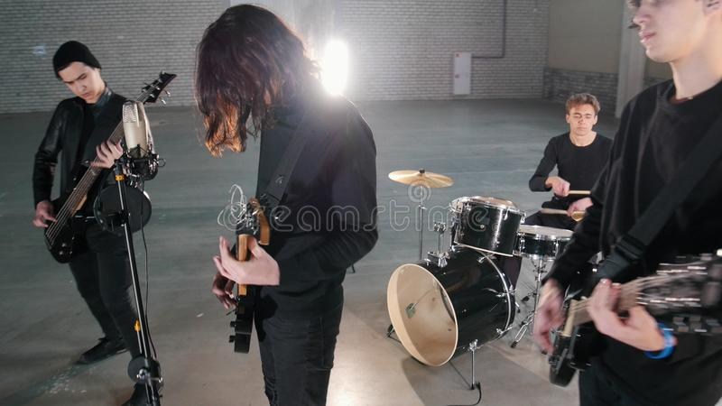 A young rock group having a repetition in a garage. Members of a group wearing black clothes. Mid shot royalty free stock photo