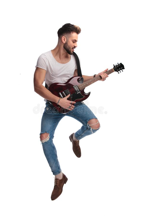 Young rock star jumping while playing during a concert stock images
