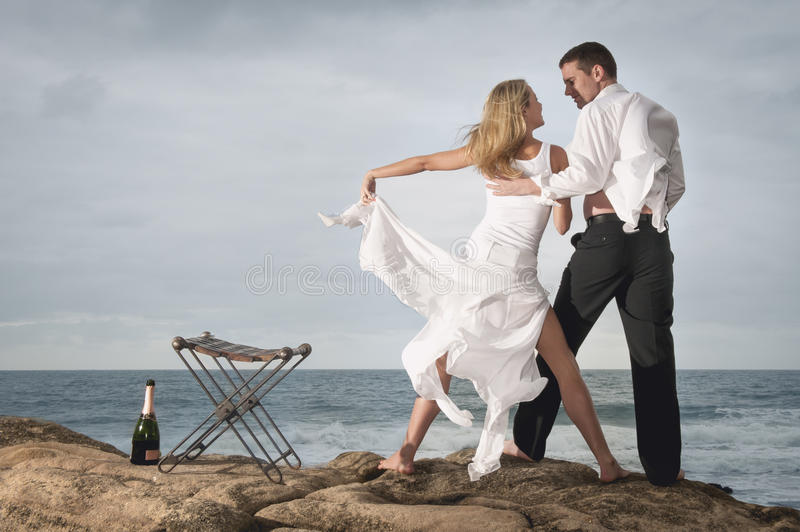 Young romantic couple dancing on beach rocks with champagne royalty free stock photography
