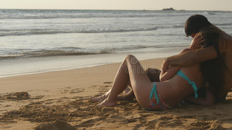 Young romantic couple is enjoying beautiful view sitting on the beach and hugging. A woman and a man sits together in stock photos